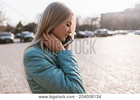 Telecommunications in big city. Girl on street. Pleasant conversation, nature concept