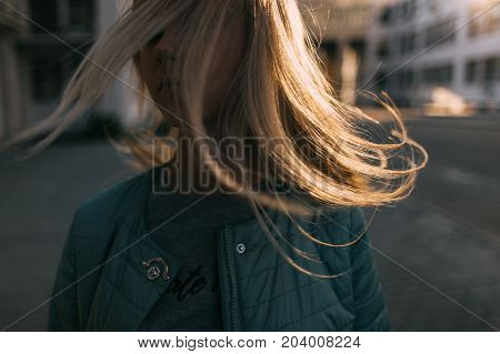 Girl portrait with windy hair in motion closeup. Easiness after break up, young independent woman in city