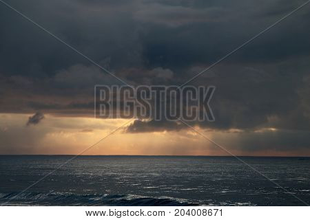 Sunrays piercing through dark clouds and shining over the vast Indian Ocean seen from Sri Lanka