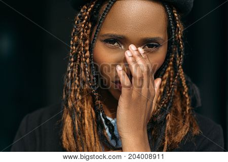Shy young black female. Embarrassed girl. Stylish haircut, ashamed pretty woman covering face on dark background, hesitation concept
