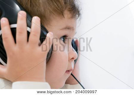 Pop Music. Happy Smiling Newborn Baby Listens To Music In Headphones On Gray Background. Cheerful Ch