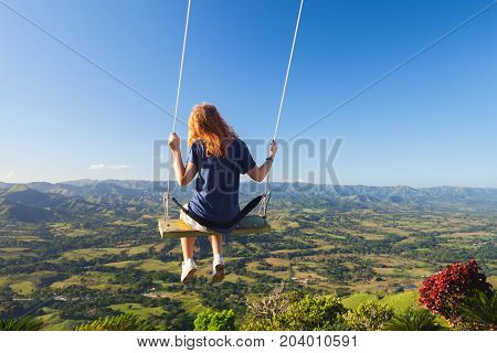 Red Haired Teenage Girl On A Swing