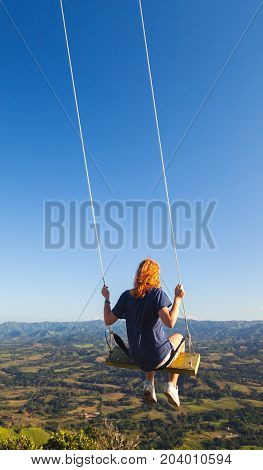 Red Haired Teenage Girl Swinging On A Swing