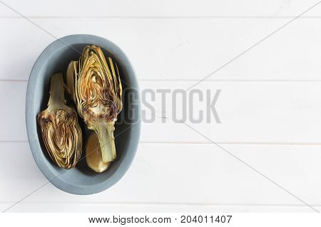 Artichokes and lemons on the plate. This product has one of the highest antioxidant capacities. Traditional vegetables in italian cuisine