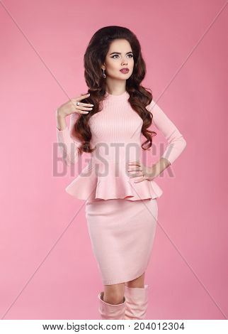 Fashionable dressed woman in pink dress. Young beautiful gorgeous female model posing  isoated on studio background. Three quarter length photo shot.