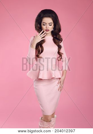 Fashion photo of beautiful young sexy woman in pink dress posing. Elegant lady. Three quarter length studio shot on studio background.