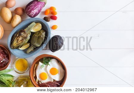 Organic food on the white table. Artichokes and lemons in the plate. Fried eggs and vegetables. This products usually use for healthy lunch. Image contains copy space for your text