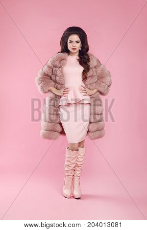 Fashion woman in fur coat and leather high boots, lady portrait over pink studio background. Fashionable beautiful brunette model in winter style.