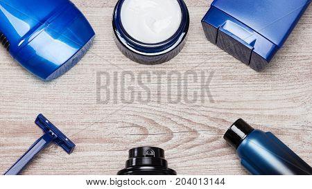 Cosmetics for men frame. Antiperspirant deodorant, face cream, shower gel, razor, shaving foam and aftershave lotion