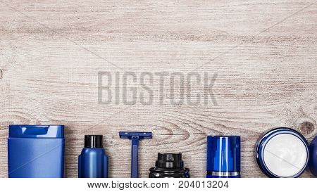 Cosmetics for men background. Row of different cosmetic products for men on shabby wooden surface, free space for text