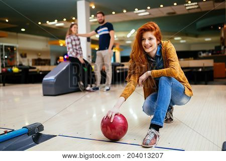Happy friends having fun and enjoying playing bowling together