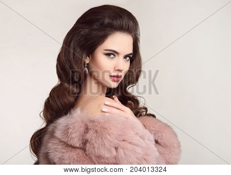 Fashion woman in pink fur coat, lady portrait. Luxury glamour girl model with elegant hairstyle.