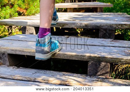 Hiking woman with boots on wooden trail - walking in mountains outdoors activity