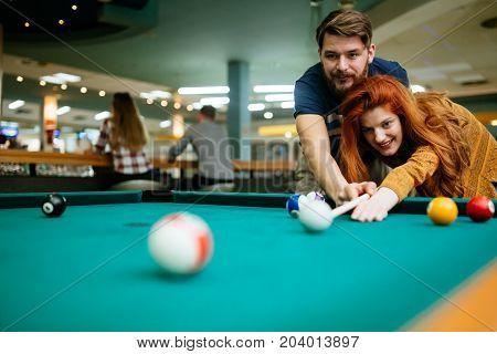 Couple in love enjoying playing billiard in snooker bar
