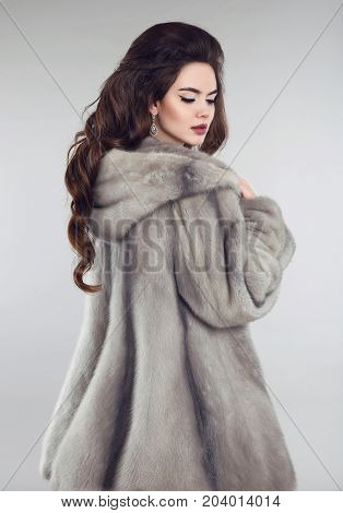 Fashionable woman in mink fur coat over studio gray background. Winter portrait of brunette girl with cowl.