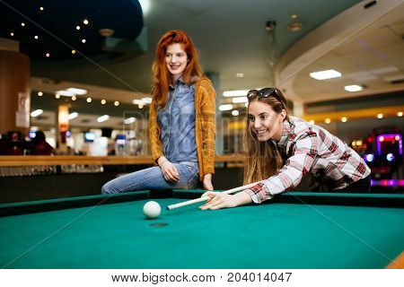 Happy friends playing snooker and billiards at club