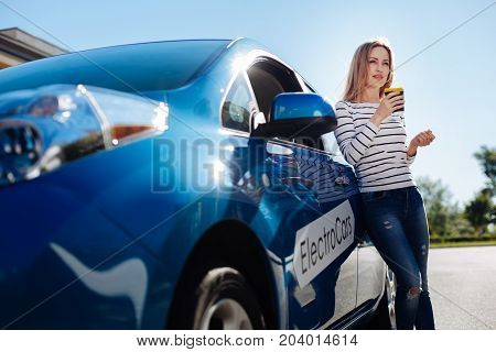 My favourite drink. Nice attractive blonde woman standing near her electro car and holding a cup of coffee while drinking it