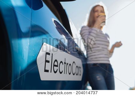 Electro car. Selective focus of a car inscription with a positive delighted attractive woman leaning on this car in the background