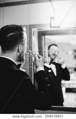 Handsome stylish groom with beard and mustache getting dressed and preparing for the wedding day.