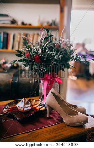 Wedding bride's wedding accessories. Wed rings and shoes. Ceremony flowers.