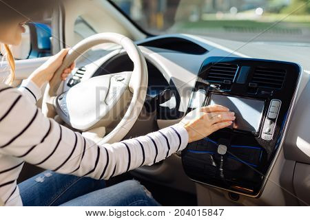Modern innovative car. Nice good looking young woman sitting in the car and using a control panel while starting it