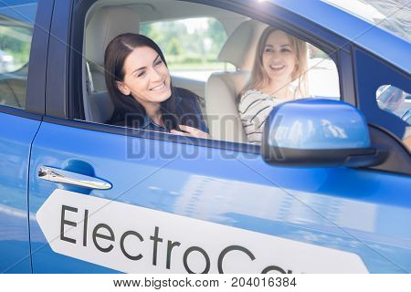 Pleasant ride. Happy nice attractive woman looking out of the window and smiling while sitting in the car with her friend