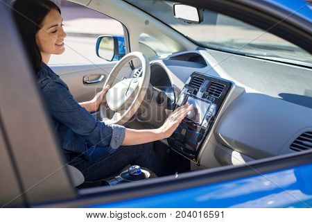 Female driver. Beautiful nice smart woman sitting in her car and smiling while starting it
