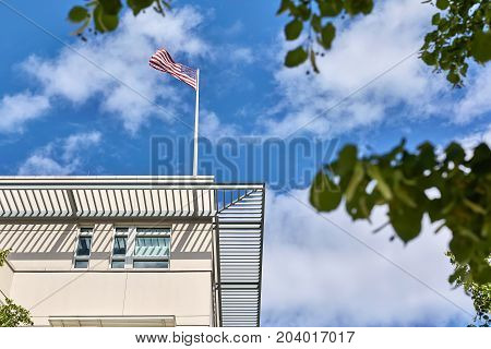 View at the top of the United States embassy on the background of the blue sky with clouds and green tree branches. On the building's roof flutters the flag of USA. Horizontal.