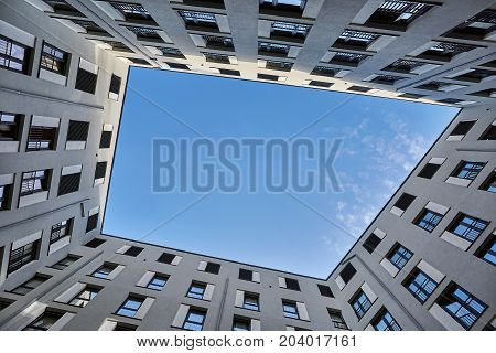 Modern geometric gray house on the blue sky with clouds background. Sun shines onto its top. View from downward. Horizontal.