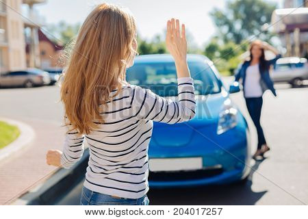 Hello dear. Attractive positive blonde woman looking at her friend and waving with her hand while greeting her
