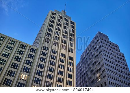 Two business buildings with few luminous windows on the evening sky background. One building has a spire. Horizontal.