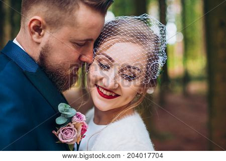 wedding copule. Beautiful bride and groom. Just merried. Close up. Happy bride and groom on their wedding hugging. Groom and Bride in a park. wedding dress. Bridal wedding bouquet of flowers Newlyweds