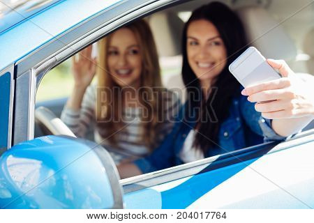 Modern technology. Selective focus of a modern smartphone being used by happy delighted women while taking a selfie