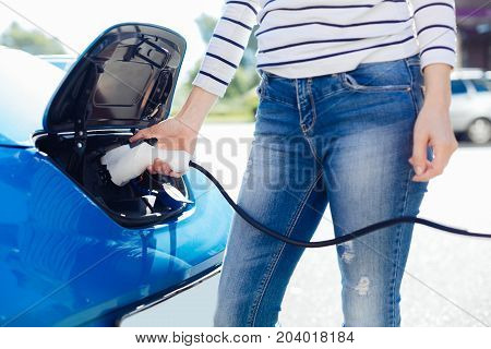New age of cars. Nice positive young woman standing near her car and holding a charger while charging the vehicle