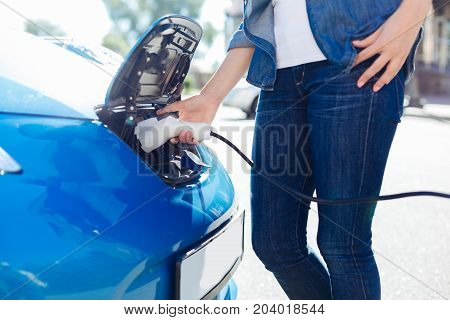 Electricity supply. Good looking skillful female driver standing near her car and holding an electric charger while using it