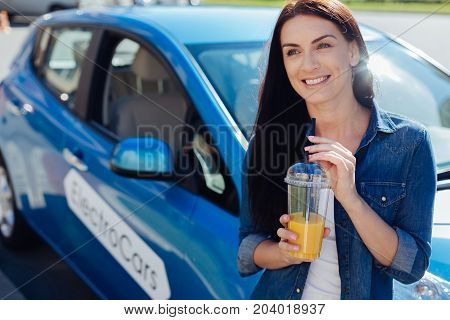 Healthy lifestyle. Happy positive brunette woman smiling and holding a cup with orange juice while standing near her car