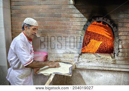 Fars Province Shiraz Iran - 18 april 2017: Baker with dough on a shovel stands near stone oven.