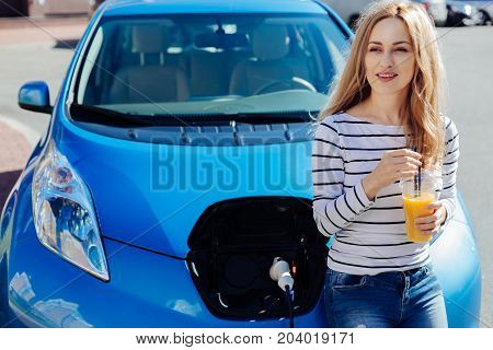 Modern car. Positive happy nice woman leaning on her car and holding a cup of juice while waiting for her car to be charged