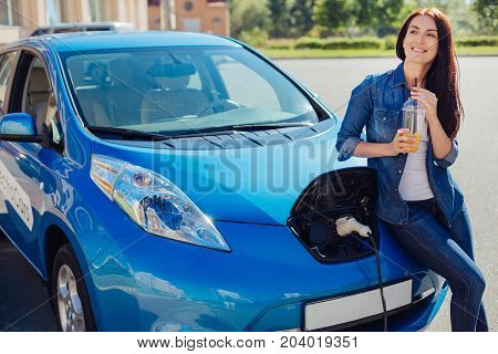 Fresh juice. Happy delighted attractive woman enjoying her drink and smiling while standing near her electro car