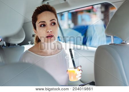 Healthy drink. Positive delighted young businesswoman holding a cup with juice and drinking it while riding on a taxi for work