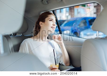 Taxi ride. Thoughtful smart attractive businesswoman sitting in the car and holding a cup with juice while going for work