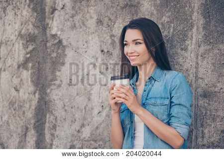 Good morning! Cheerful pretty young serene brunette lady is having hot tea near concrete wall outside smiling wearing cozy casual outfit