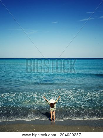 Young girl rising her hands to the sky and admiring the ocean.