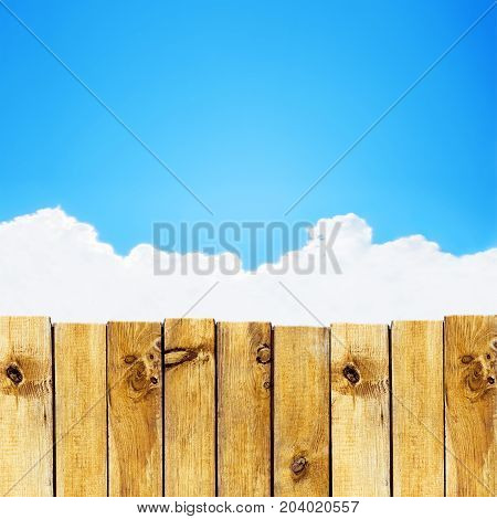 Wooden fence against blue sky with cloud background