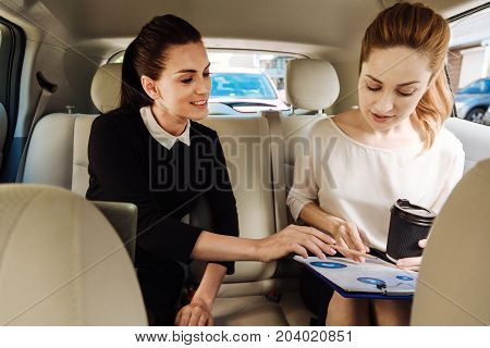 Pleasant cooperation. Delighted nice intelligent businesswomen sitting in the car and talking to each other while working together