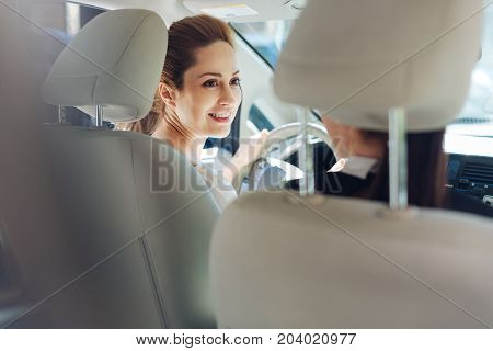 Pleasant communication. Cheerful happy nice women looking at each other and having conversation while riding a car
