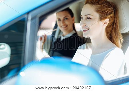 Confident driver. Attractive nice cheerful businesswoman smiling and looking in front of her while driving a car