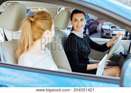 Importance of safety. Joyful positive delighted woman driving a car and wearing a seat belt while thinking about her safety