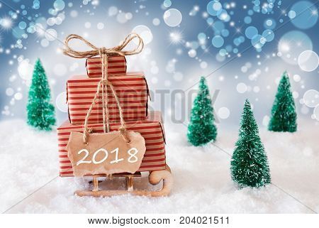 Sleigh Or Sled With Christmas Gifts Or Presents. Snowy Scenery With Snow And Trees. Blue Sparkling Background With Bokeh Effect. Label With Text 2018 For Happy New Year