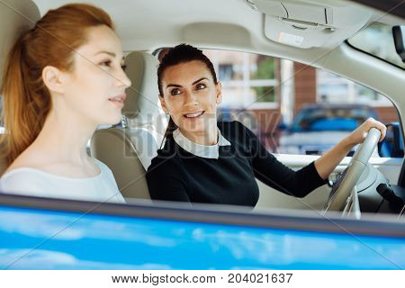 Professional relationships. Positive nice attractive businesswoman sitting behind the wheel and looking at her colleague while going to work with her